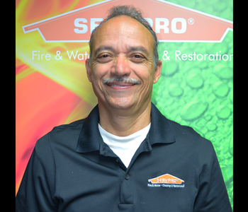 Hugo standing in front of a SERVPRO banner