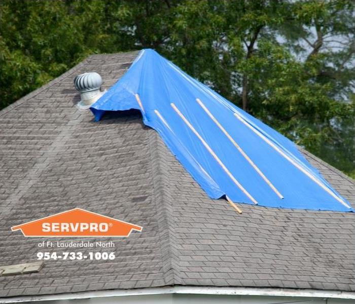 Tarp covering damage on the roof of a house.