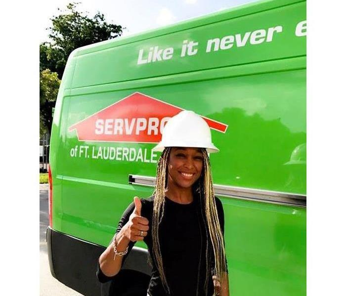 female manager in hard hat in front of a SERVPROtruck