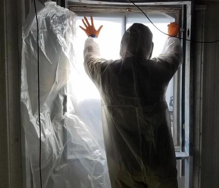 Person in protective suit covering window in room full of mold